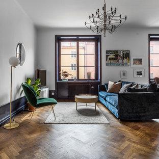 Exempel på ett stort minimalistiskt allrum med öppen planlösning, med vita väggar, mellanmörkt trägolv, brunt golv och en fristående TV
