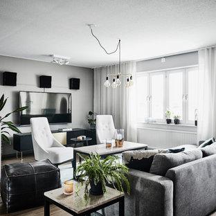 Inredning av ett modernt stort separat vardagsrum, med grå väggar, mellanmörkt trägolv, en väggmonterad TV och brunt golv