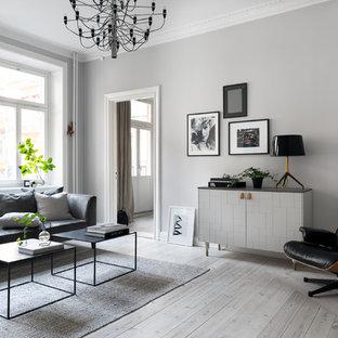 Skandinavisk inredning av ett vardagsrum, med grå väggar, ljust trägolv och beiget golv