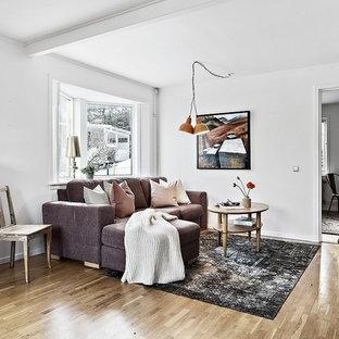 Inredning av ett nordiskt litet separat vardagsrum, med vita väggar, mellanmörkt trägolv och beiget golv