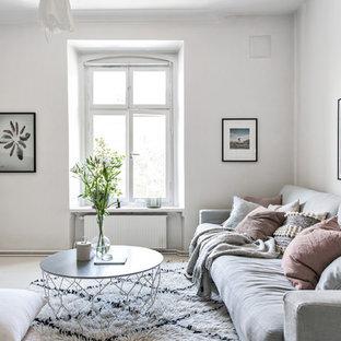 Bild på ett nordiskt vardagsrum, med vita väggar och beiget golv