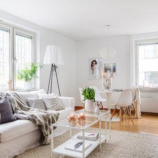 Exempel på ett mellanstort skandinaviskt allrum med öppen planlösning, med vita väggar, ljust trägolv och beiget golv