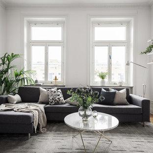 Idéer för nordiska vardagsrum, med vita väggar, mellanmörkt trägolv och brunt golv