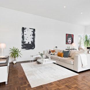 Bild på ett mellanstort minimalistiskt allrum med öppen planlösning, med vita väggar, en väggmonterad TV, brunt golv och mellanmörkt trägolv