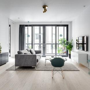 Skandinavisk inredning av ett mellanstort allrum med öppen planlösning, med vita väggar, en väggmonterad TV, ett finrum och ljust trägolv
