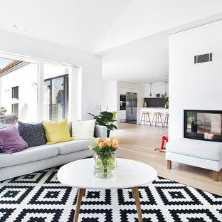 Cette image montre un grand salon nordique ouvert avec une salle de réception, un mur blanc, une cheminée double-face, un sol en bois clair et aucun téléviseur.