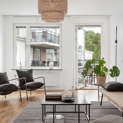 Living room - mid-sized scandinavian enclosed and formal light wood floor living room idea in Stockholm with white walls and no tv
