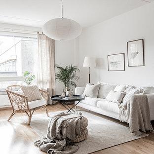 Esempio di un soggiorno nordico di medie dimensioni e chiuso con pareti bianche, pavimento beige, sala formale e parquet chiaro