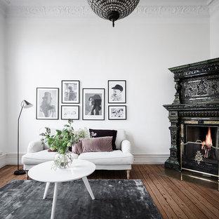 Bild på ett skandinaviskt separat vardagsrum, med ett finrum, vita väggar, mörkt trägolv, en öppen hörnspis, en spiselkrans i trä och brunt golv