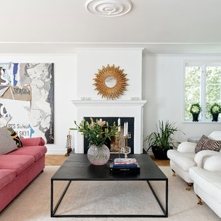 Klassisk inredning av ett stort allrum med öppen planlösning, med ett finrum, vita väggar, en standard öppen spis och ljust trägolv