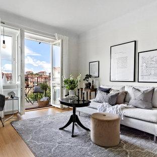 Exempel på ett minimalistiskt allrum med öppen planlösning, med vita väggar och mellanmörkt trägolv
