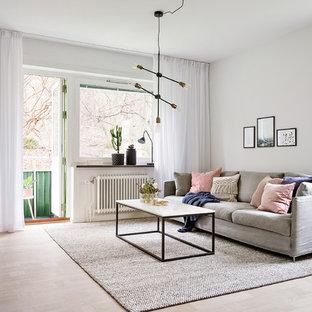 Bild på ett minimalistiskt vardagsrum, med vita väggar, ljust trägolv och beiget golv
