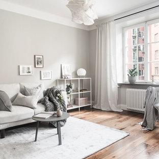 Exempel på ett skandinaviskt allrum med öppen planlösning, med grå väggar och mellanmörkt trägolv