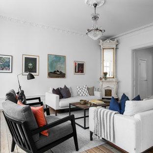 Foto på ett mellanstort vintage vardagsrum, med vita väggar, ljust trägolv, en öppen vedspis, en spiselkrans i trä och beiget golv