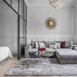 Inredning av ett klassiskt litet vardagsrum, med grå väggar, mellanmörkt trägolv och brunt golv