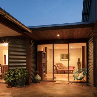 Foto di un portico eclettico di medie dimensioni e davanti casa con pedane e un tetto a sbalzo