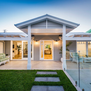 Inspiration for a mid-sized beach style front yard verandah in Gold Coast - Tweed with a pergola and tile.