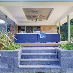 Foto di un grande portico tropicale dietro casa con lastre di cemento e un tetto a sbalzo