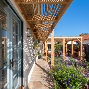 Tuscan stone back porch photo in Melbourne with a pergola