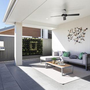 Exempel på en modern veranda på baksidan av huset, med en vertikal trädgård, betongplatta och takförlängning