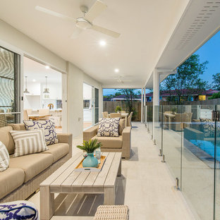 Inspiration for a mid-sized beach style backyard verandah in Brisbane with a roof extension and tile.