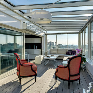 Idée de décoration pour une grand véranda design avec un sol en bois clair, aucune cheminée et un plafond en verre.