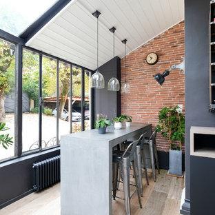 Réalisation d'une véranda urbaine avec un sol en bois brun, aucune cheminée et un plafond standard.