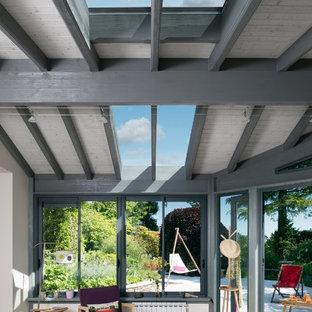 Idée de décoration pour une véranda design de taille moyenne avec aucune cheminée et un puits de lumière.