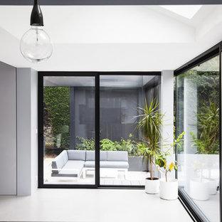 Aménagement d'une véranda contemporaine de taille moyenne avec béton au sol, aucune cheminée et un puits de lumière.
