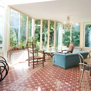 Réalisation d'une grand véranda champêtre avec un sol en carrelage de céramique, aucune cheminée et un plafond standard.