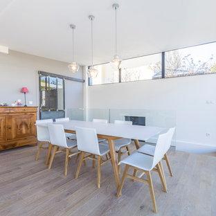 Réalisation d'une grande véranda design avec un sol en bois clair, un plafond standard et un sol beige.