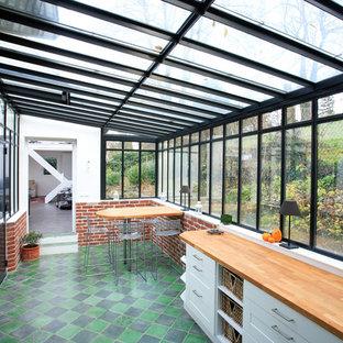 Immagine di una grande veranda industriale con nessun camino, soffitto in vetro e pavimento multicolore