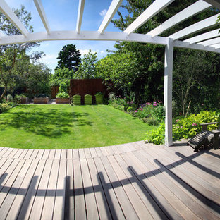 Large classic porch idea in London with decking and a pergola
