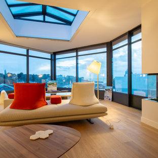 Modern inredning av ett mellanstort uterum, med ljust trägolv, en öppen hörnspis, en spiselkrans i gips, takfönster och beiget golv