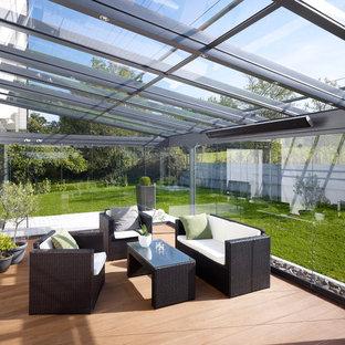 Cette image montre une grande véranda design avec un plafond en verre, un sol en bois clair et aucune cheminée.