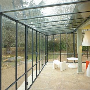 Ejemplo de galería actual, de tamaño medio, con suelo de baldosas de terracota, suelo beige y techo de vidrio