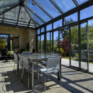 Aménagement d'une grand véranda classique avec un sol en carrelage de porcelaine, aucune cheminée et un plafond en verre.