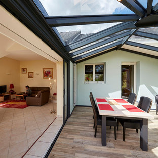 Photo of a contemporary conservatory in Other with laminate floors, no fireplace, a skylight and beige floors.