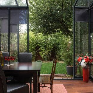 Idée de décoration pour une véranda design de taille moyenne avec un sol en bois brun, aucune cheminée et un plafond en verre.