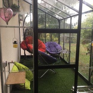 Idee per una veranda bohémian di medie dimensioni con moquette, soffitto in vetro e pavimento verde