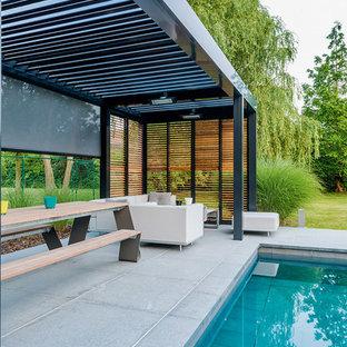 Ispirazione per un grande portico design dietro casa con un portico chiuso, piastrelle e una pergola