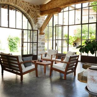Aménagement d'une grand véranda méditerranéenne avec béton au sol, aucune cheminée et un plafond standard.