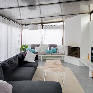 Modern inredning av ett stort uterum, med betonggolv, en öppen hörnspis, en spiselkrans i gips, tak och grått golv