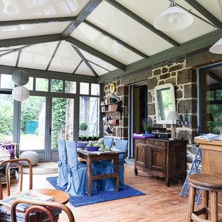 Cette image montre une véranda rustique avec un sol en bois brun et un plafond standard.