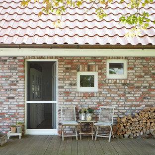 Mittelgroße, Überdachte Landhaus Veranda neben dem Haus mit Kübelpflanzen und Dielen in Bremen