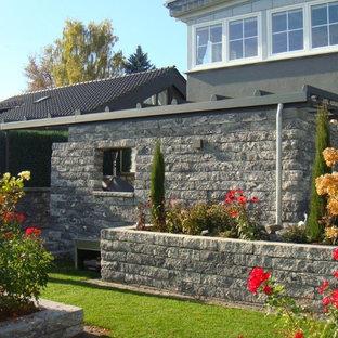 Immagine di un portico country di medie dimensioni e dietro casa con pavimentazioni in pietra naturale e un parasole