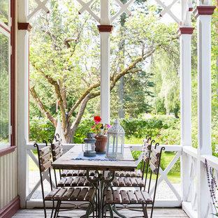 Bild på en lantlig veranda framför huset, med trädäck och en pergola