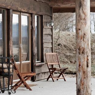 Idéer för en mellanstor rustik veranda framför huset, med betongplatta och takförlängning