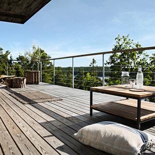 Foto di un patio o portico scandinavo di medie dimensioni e dietro casa con pedane e un tetto a sbalzo