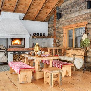 На фото: веранда в стиле рустика с летней кухней, навесом и настилом с